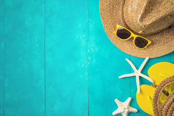 Summer holiday vacation concept with beach accessories over blue wooden background. Top view from above