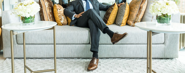 richness and success concept. business man sitting on a leather couch, putting his foot on the leg