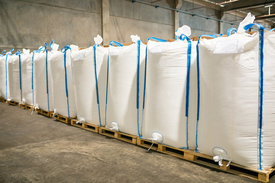 Rows or stacks of white sack bags at large warehouse in modern factory. Packaging in factory or warehouse