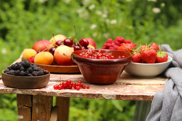 organic berries peaches, raspberries and strawberries on a wooden table
