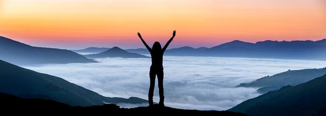 Fototapeta Glückliche Frau auf einem Gipfel über der Nebeldecke obraz
