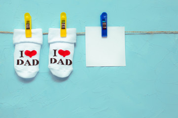 Socks with the inscription I love dad hanging on a clothespin on a rope. Concept newborn. Mockup