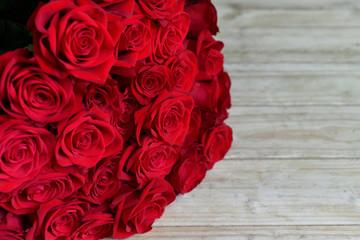 Fototapeta Bukiet czerwonych roż na drewnianym stole obraz
