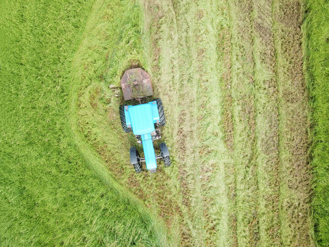 Aerial view of a tractor bush hogging on a field in a farm