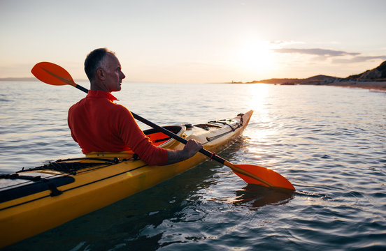 Senior man paddling kayak on the sunset sea
