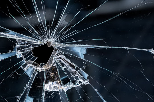 Closeup of a broken window. Cracks radiate from the break, and there is an irregular hole near the center.