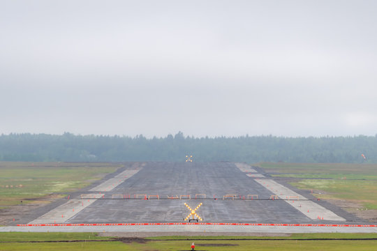 Closed runway at an airport on an overcast, foggy day. The runway has a large illuminated warning X sign at each end, and is blocked by sawhorses.