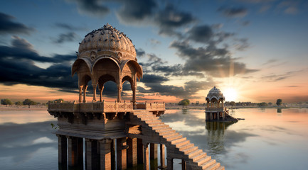 Fototapete - Gadi Sagar temple gazebo on Gadisar lake at sunset Jaisalmer, Rajasthan, India