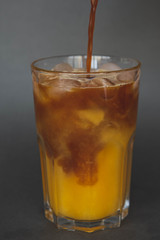 A large transparent glass filled with cold summer drink Latte with orange juice cooked in a coffee shop of the third wave. gray, isolated background, photo for the menu