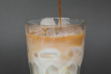 A large transparent glass filled with cold summer drink Latte with ice cooked in a third wave coffee shop is photographed on a gray, isolated background, photo for the menu