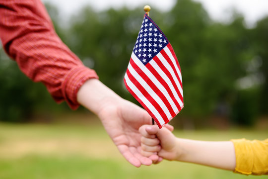 Young woman and little child holding american flag. Independence Day concept.