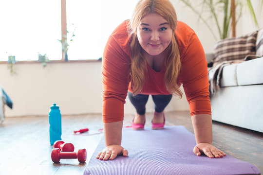 Chubby woman sport at home standing on arms on mat looking camera happy