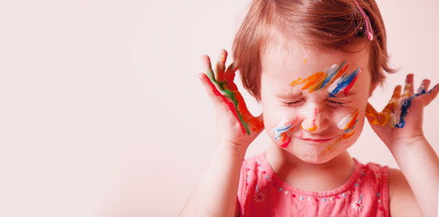 Art, creative and happiness childhood concept. Colorful painted hands and face in a beautiful little child girl.