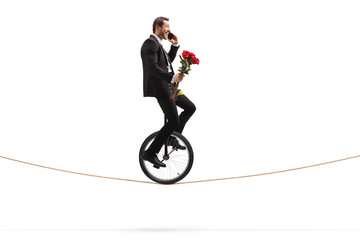 Businessman with roses talking on a phone and riding a unicycle on a rope