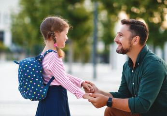 first day at school. father leads  little child school girl in first grade.