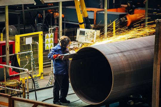 Worker cleans welded seam on steel pipe using grinding machine in metalwork workshop