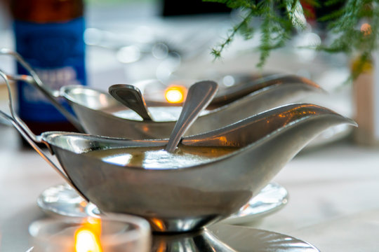 detailed shot of luxury silver gravy bowls containing salad dressing at a banquet for a wedding party.  the romantic dinner is elegant with white table cloth and decorative plate wear