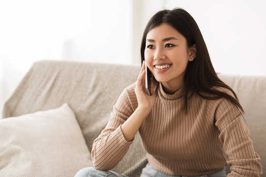 Asian Girl Talking on Mobile Phone and Smiling
