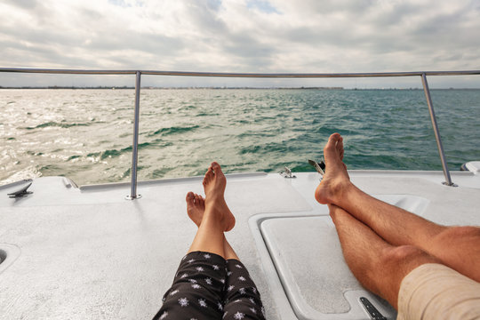 Yacht boat lifestyle couple relaxing on cruise ship in Hawaii holiday . Two tourists feet relax getaway enjoying summer vacation.