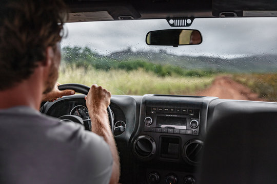 Man driver driving off road trail path with 4x4 car on adventure trip travel holiday. Hawaii drive in the rain bad weather.
