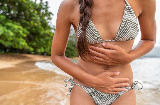 Stomach bug travel disease woman tourist with painful cramps on tropical beach - norovirus gastroenteritis concept. Cramp pain health insurance.