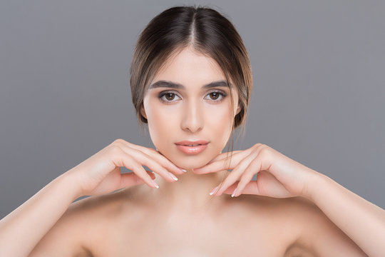 Young beautiful woman with perfect skin massaging her face