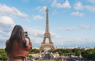 Wall Mural - Traveler woman taking photo of Eiffel Tower, famous landmark and travel destination in Paris, France by mobile smartphone