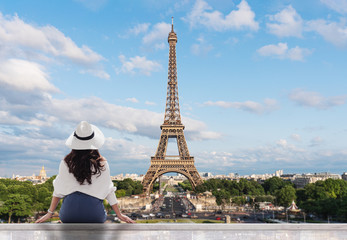 Papiers peints Tour Eiffel Young traveler woman in white hat looking at Eiffel tower, famous landmark and travel destination in Paris