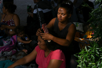 Asylum seekers waiting in hopes of being let through the nearby U.S. port of entry pass the time in a makeshift migrant camp in Matamoros