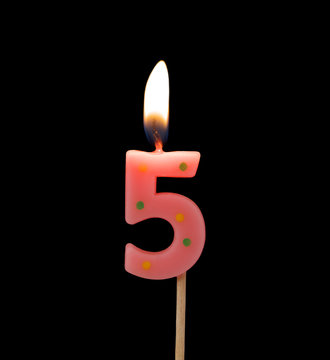 Burning birthday candle isolated on black background, number 5