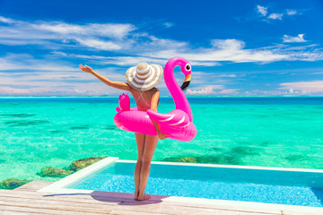 Vacation Woman in bikini and inflatable pink flamingo toy mattress float by pool