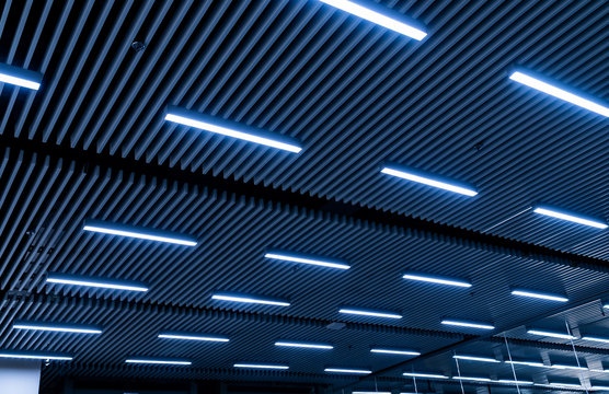 Leading lines and low light view. Fluorescent lamps open in row on the ceiling beautiful and modern inside the building.