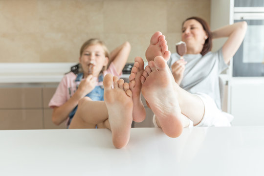 Cute girl and her mother are smiling while eating ice cream in the kitchen with legs on a table