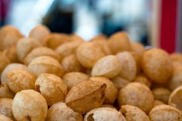 Gol gappe pani puri water balls stacked at a street food stall in Delhi inida