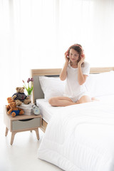 Caucasian young and beautiful woman with happy sitting on the  comfortable  double bed in the modern or minimal interior bedroom design decorated with , white bedding and wooden furniture