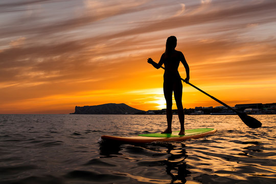 Stand up paddle boarding on a quiet sea with warm summer sunset colors.