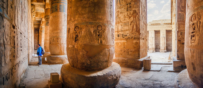 The tourist considers the hieroglyphs on the walls of the temple of Medinet Habu. Egypt, Luxor. The Mortuary Temple of Ramesses III at Medinet Habu is an important New Kingdom period structure
