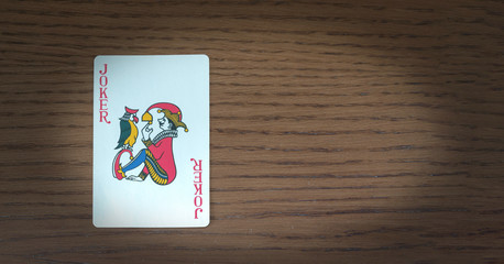 card with image of joker on wooden table, vignetted