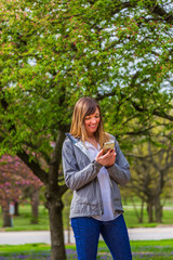 Young woman smiling while texting on her phone in a park.