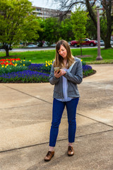Young woman standing looking at her phone in a park.