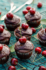 Chocolate-coffee muffins with melted dark chocolate topping with the addition of fresh cherries on ...