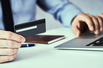 Businessman holding credit card and typing on laptop for online shopping and payment makes a purchase on the Internet.