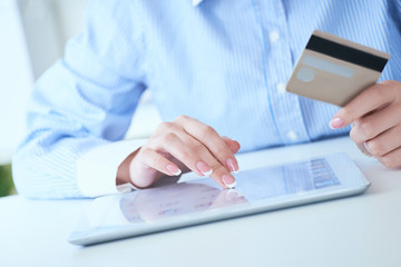 Close-up woman's hands holding a credit card and using tablet pc for online shopping. Middle...