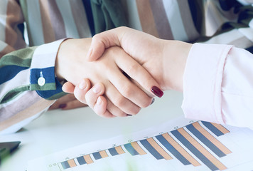 Friendly businesswoman handshaking over the office desk with economic charts after pleasant talk and effective negotiation, good relationships.