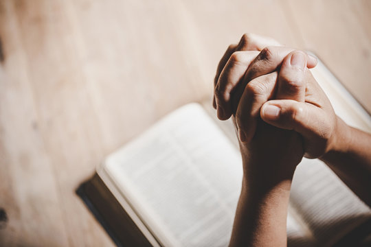 Spirituality and religion, Hands folded in prayer on a Holy Bible in church concept for faith.