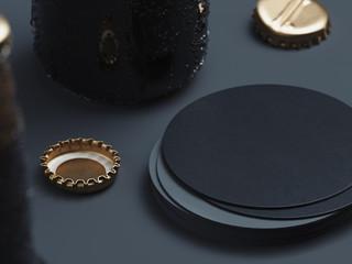 Blank round black beer coaster stack mock up and beer caps on black background. 3d rendering