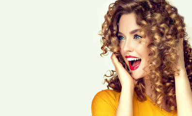 Woman surprise showing product .Beautiful girl  with curly hair  looking away . Presenting your offer. Isolated on white background. Expressive facial expressions