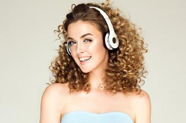 Beautiful smiling girl with small curly hair listening to music. Joyful woman in big headphones enjoying life. Afro voluminous hairstyle