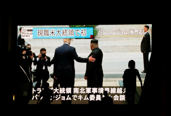 Passers-by are silhouetted as they walk past a huge screen reporting a meeting between U.S. President Donald Trump and North Korean leader Kim Jong Un at Panmunjom in the demilitarized zone, in Tokyo