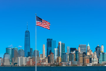 Fotomurales - Scene of Flag of America over New york cityscape river side which location is lower manhattan,Architecture and building with tourist and Independence day concept